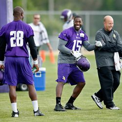 Jul 27, 2013; Mankato, MN, USA; Minnesota Vikings wide receiver Greg Jennings (15) laughs with athletic trainer Eric Sugarman as running back Adrian Peterson (28) watches in between drills at training camp  at Blakeslee Fields. Mandatory Credit: Bruce Klu