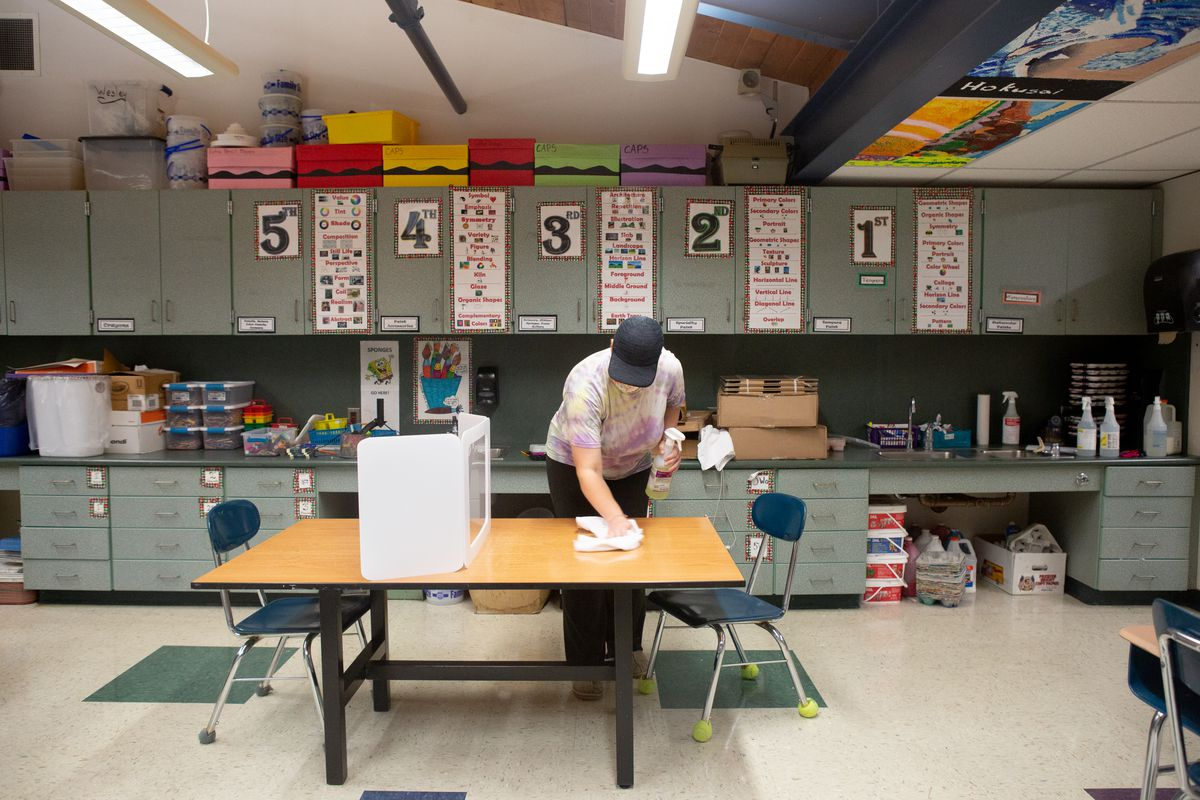 Janitorial staff member Mary Horbock cleans a desk between classes at Wesley Elementary School.