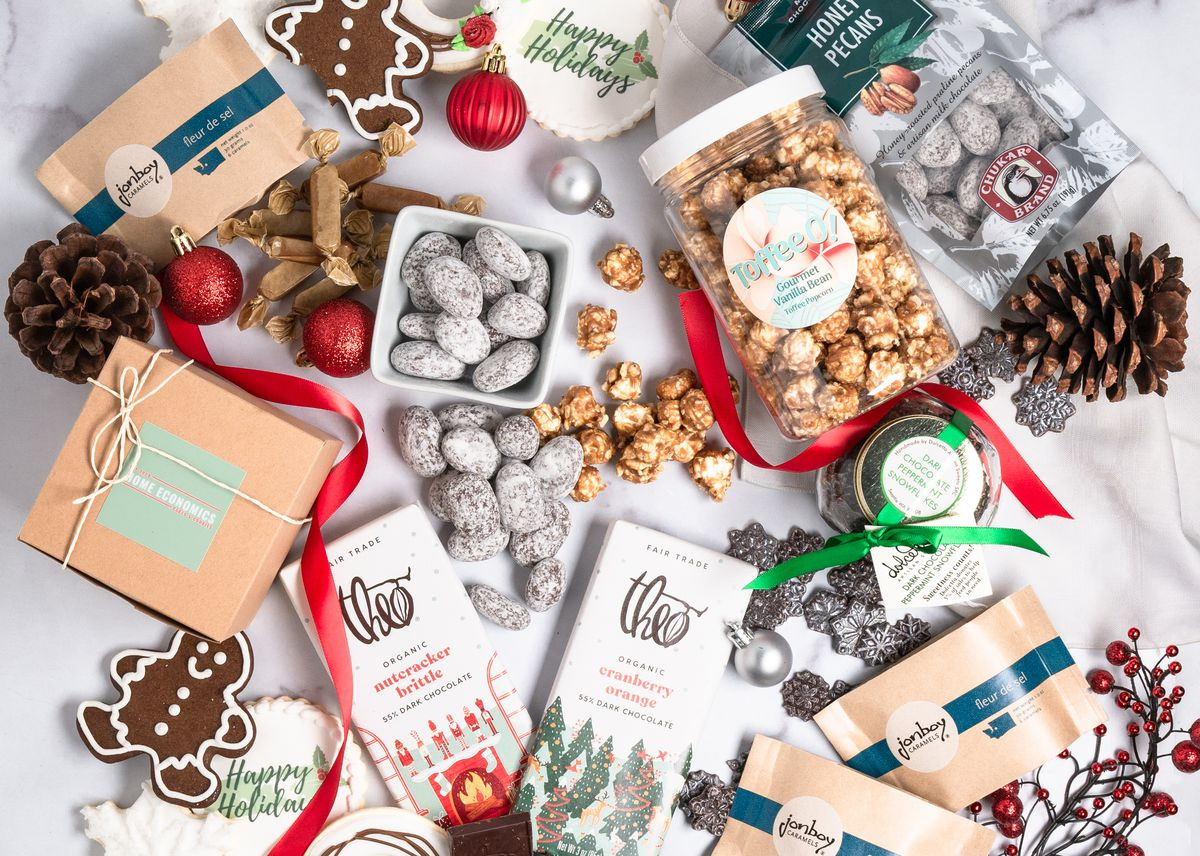 A holiday-themed dessert spread, with Theo chocolate, caramels, and other packaged goods; pine cones, gingerbread and Christmas ornaments arranged as decor