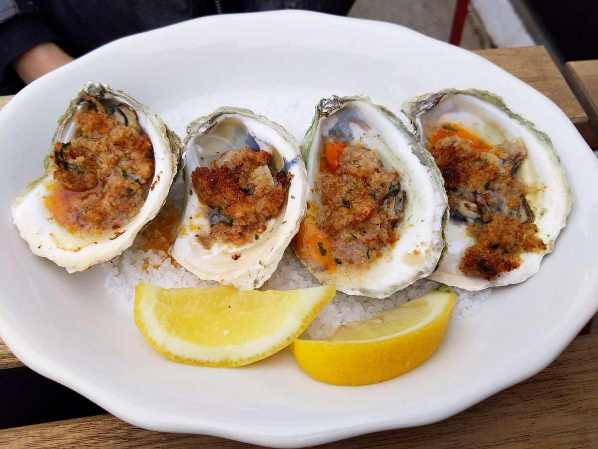 Four stuffed oysters on their shells with lemon wedges in front.