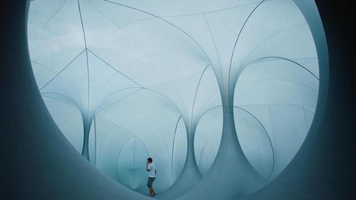 A young boy walks through tunnels of billowing canvas.