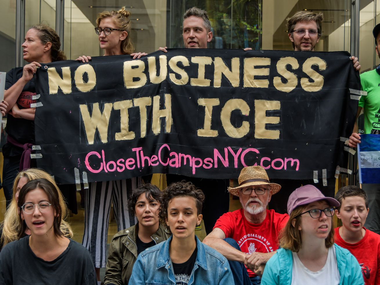 """A group of around 12 protestors holding a sign that says """"No business with ICE."""""""