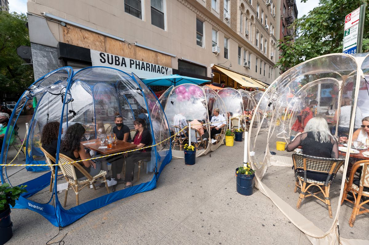 New York City residents sit in clear plastic bubble tents while dining outside.