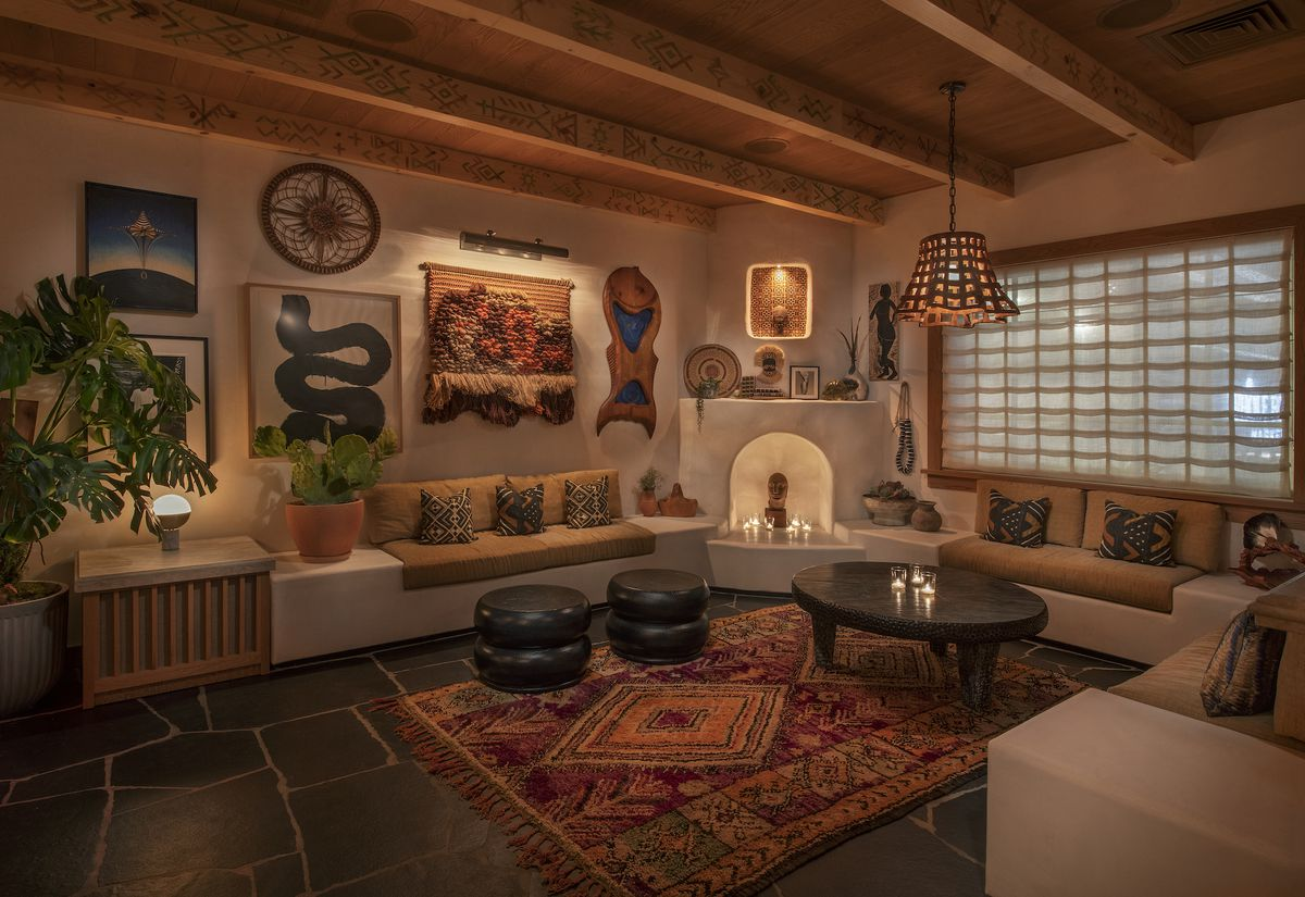 A corner lounge area with fireplace and sandstone walls.