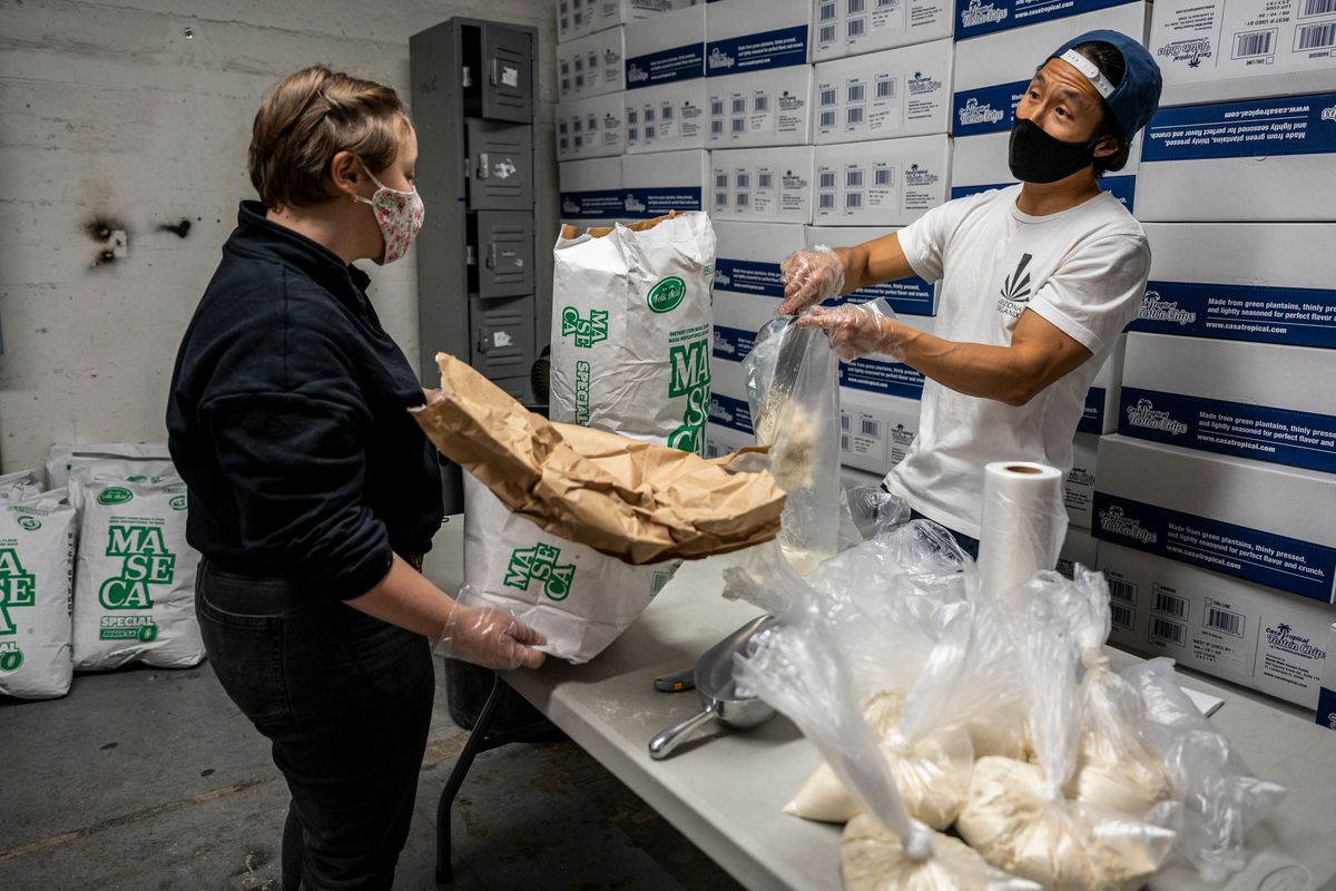 Volunteers with South Brooklyn Mutual Aid pour flour into bags at their Brooklyn Army Terminal warehouse space. Aug. 22, 2020.