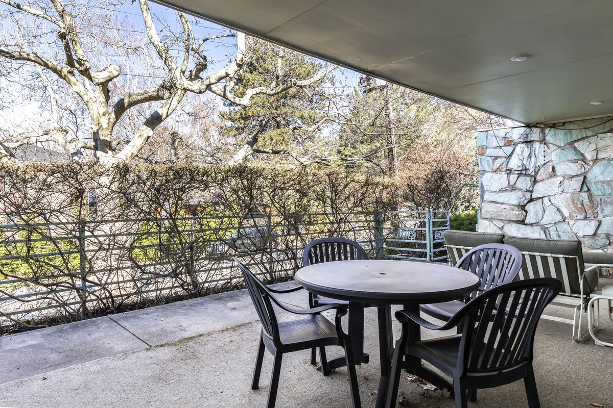 Plastic outdoor furniture sits underneath a covered stone patio.