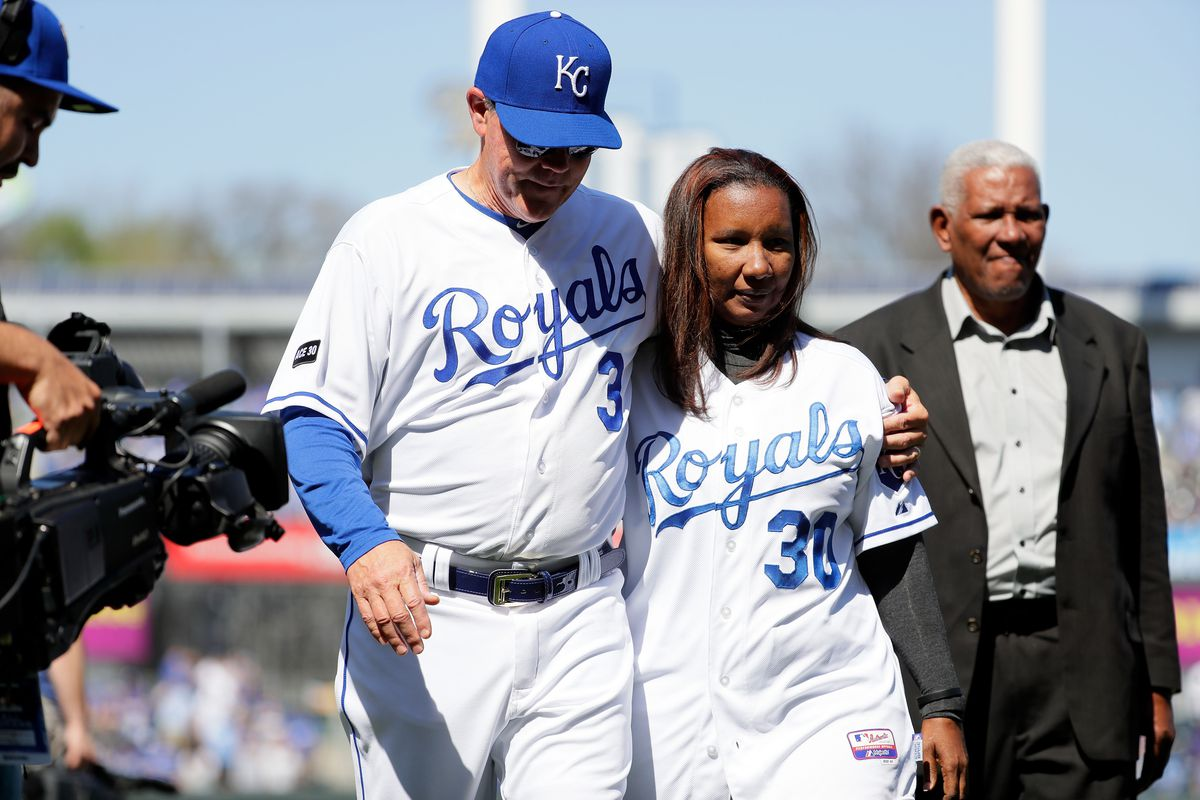 Manager Ned Yost #3 of the Kansas City Royals walks off the field with his arm around Marisol Hernandez, mother of Yordano Ventura #30, as Ventura's grandfather Raul Hernandez follows prior to the Royals 2017 home opener at Kauffman Stadium.