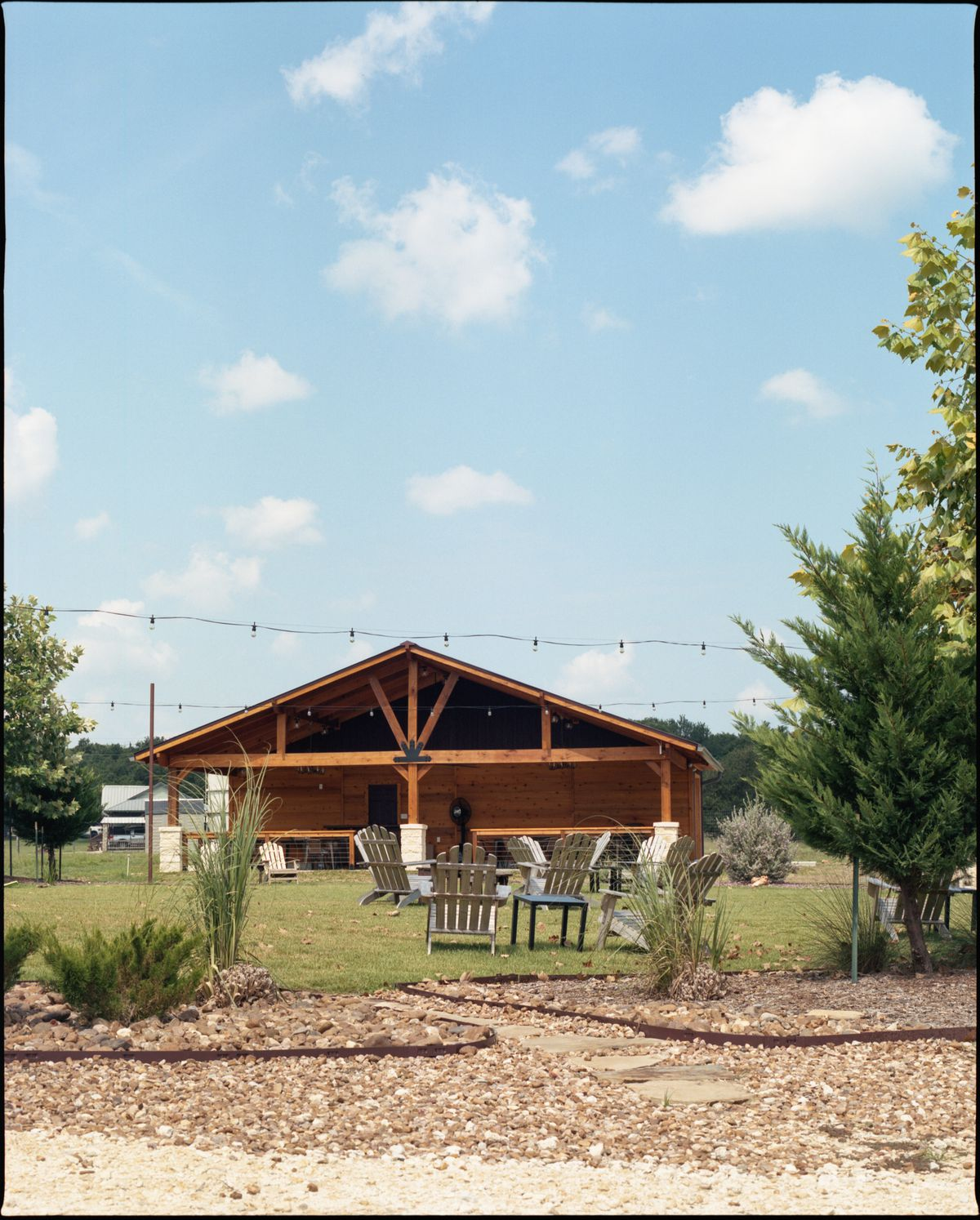 A wooden A-frame in the distance, with green grass, scattered green plants, lawn tables and chairs, and hanging string lights in the foreground.