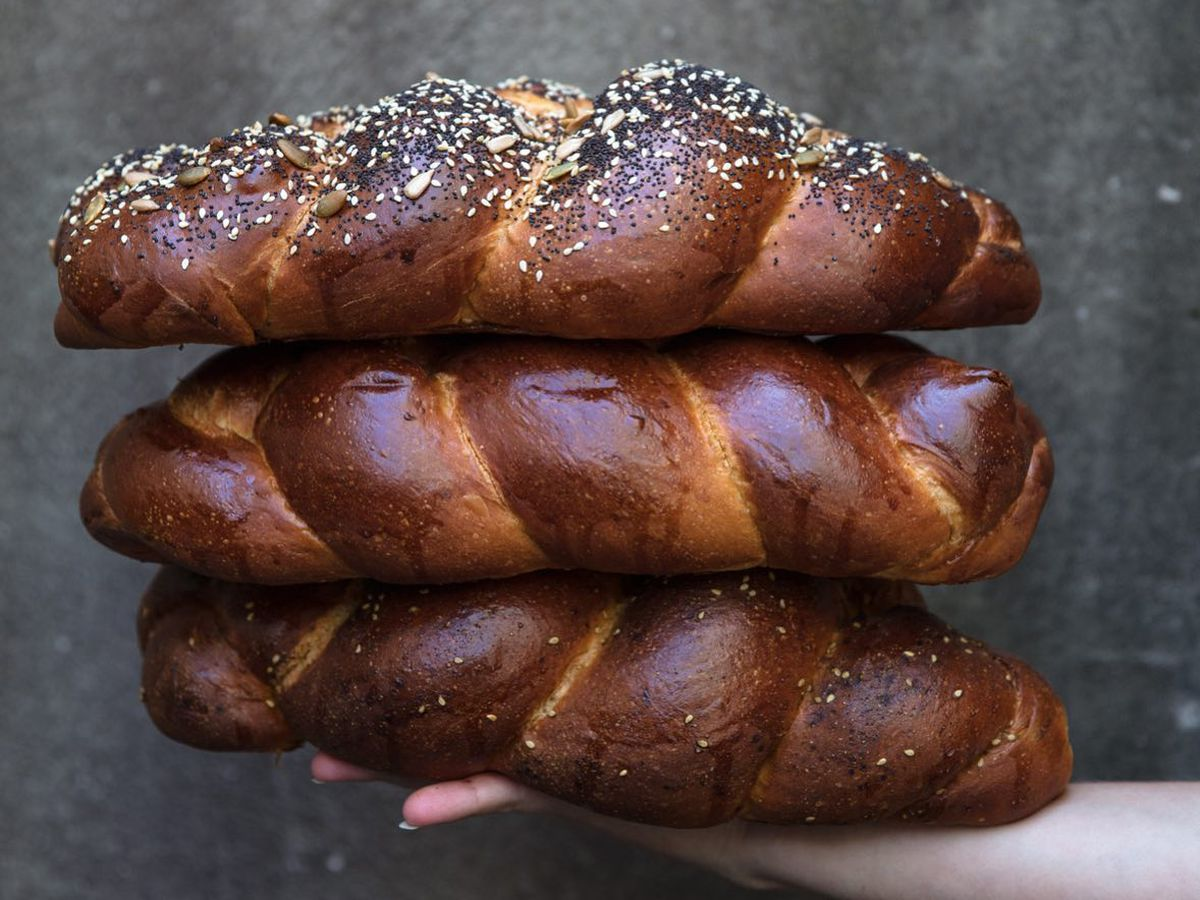three loaves of challah stacked on top of each other on a gray background