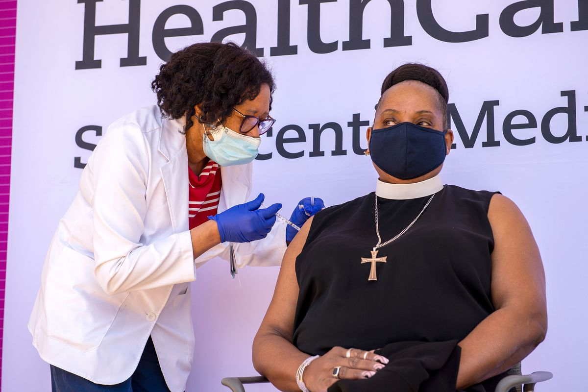 A person receives and injection in their arm from a health care worker.