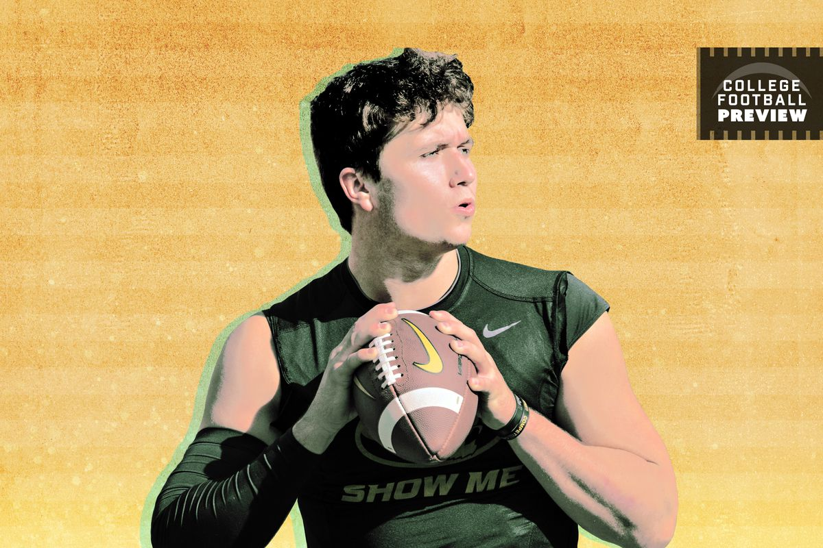 Drew Lock gripping a football with both hands