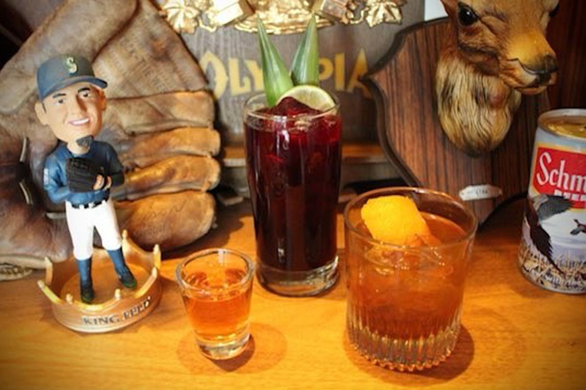 A Seattle Mariners bobblehead doll sits to the left, in front of a vintage baseball mitt; next to that are three cocktails and a can of Schmidt beer; behind the can of beer is a mounted deer's head.