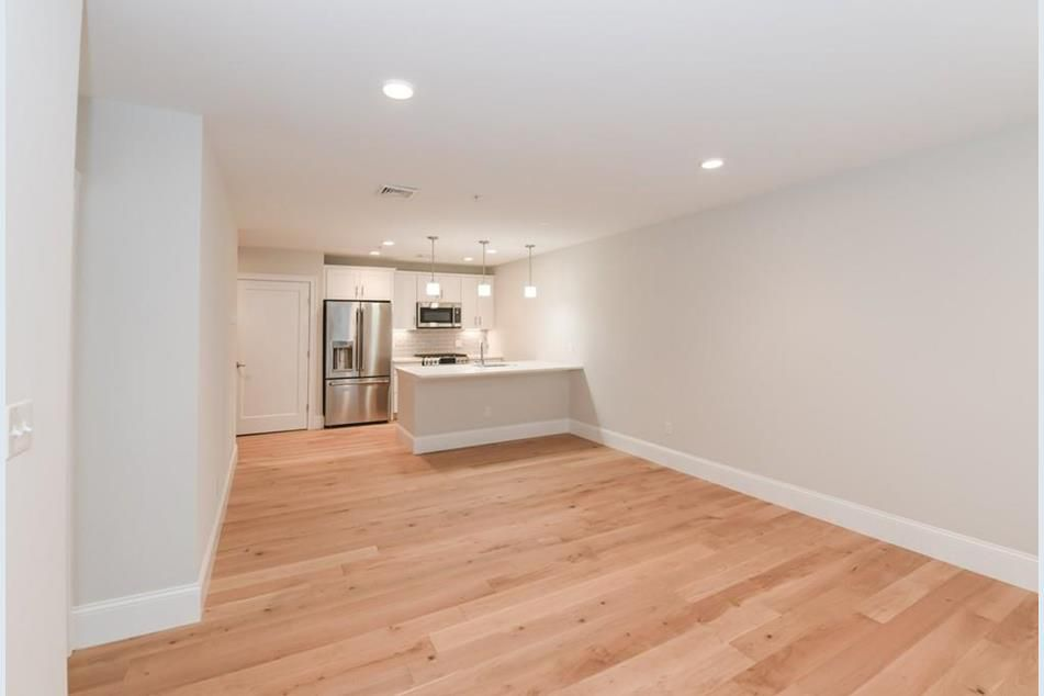 A long, empty living room-kitchen with a counter separating the two rooms.