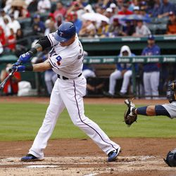 Texas Rangers' Josh Hamilton (32) hits a double in front of Seattle Mariners catcher Miguel Olivo (30) in the first inning of a baseball game Sunday, Sept. 16, 2012, in Arlington, Texas.