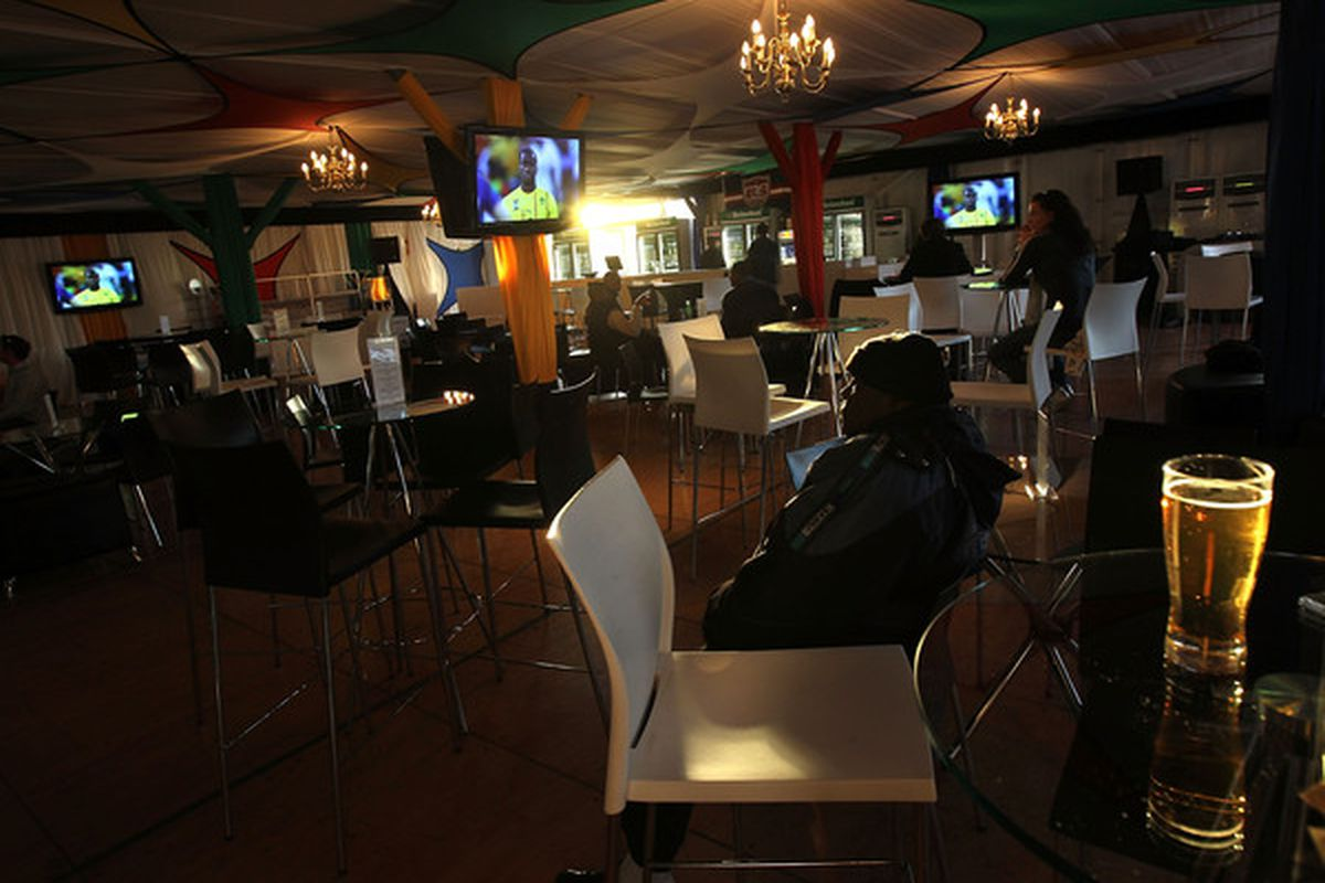 JOHANNESBURG, SOUTH AFRICA:  A Cameroon soccer fan sits in an almost empty restaurant while watching a soccer match between Cameroon and Japan. (Photo by John Moore/Getty Images)