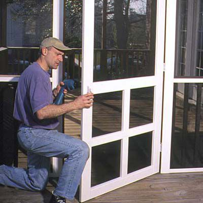Man Installs Screen Door Of Porch Screen