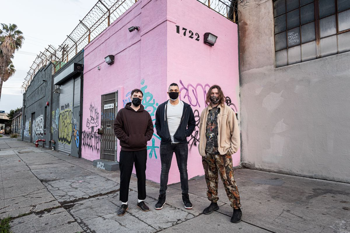 A trio of owners in front of their music venue during the day.