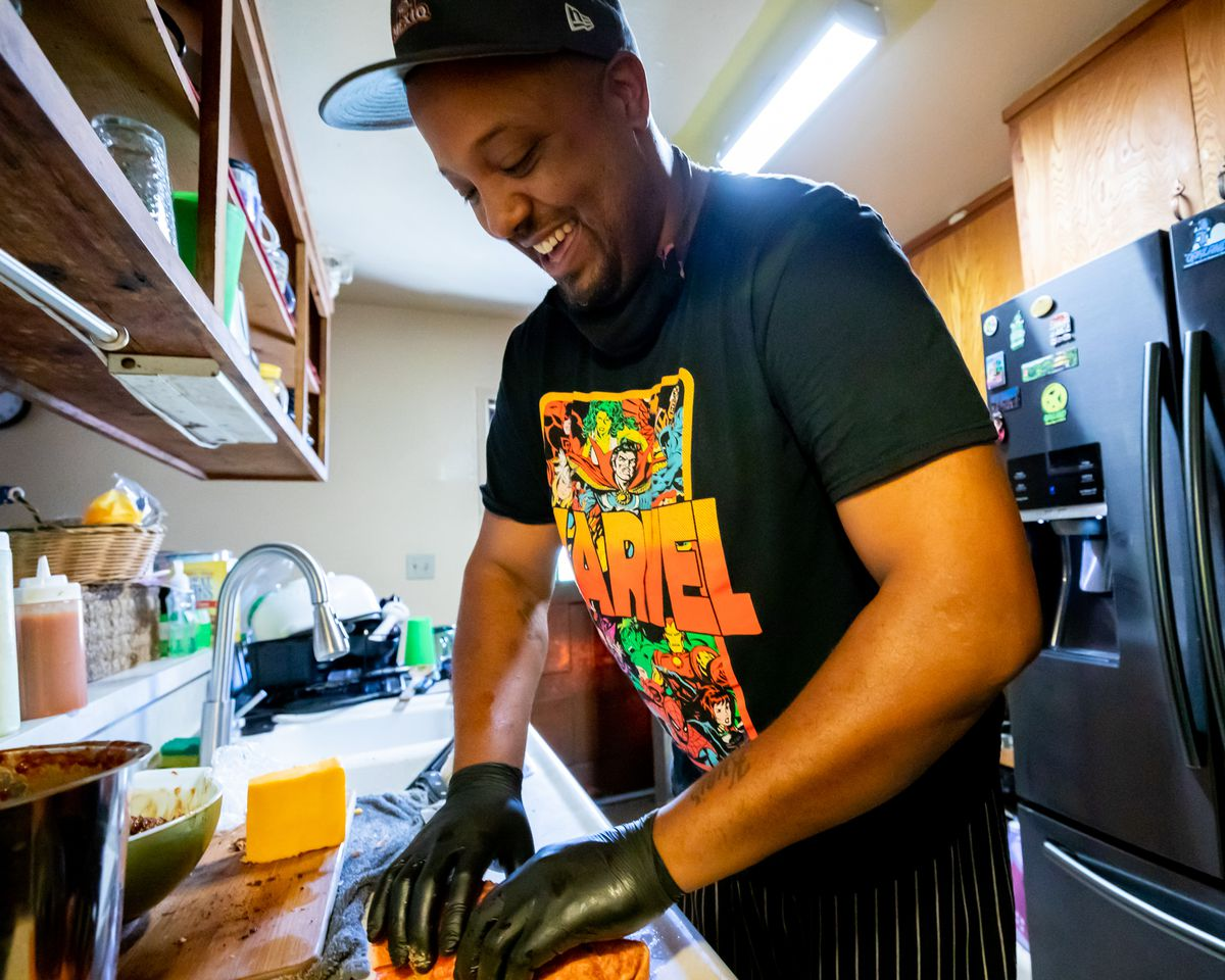 The chef, wearing black gloves and a black Marvel T-shirt, smiles widely as he rolls a burrito in his kitchen