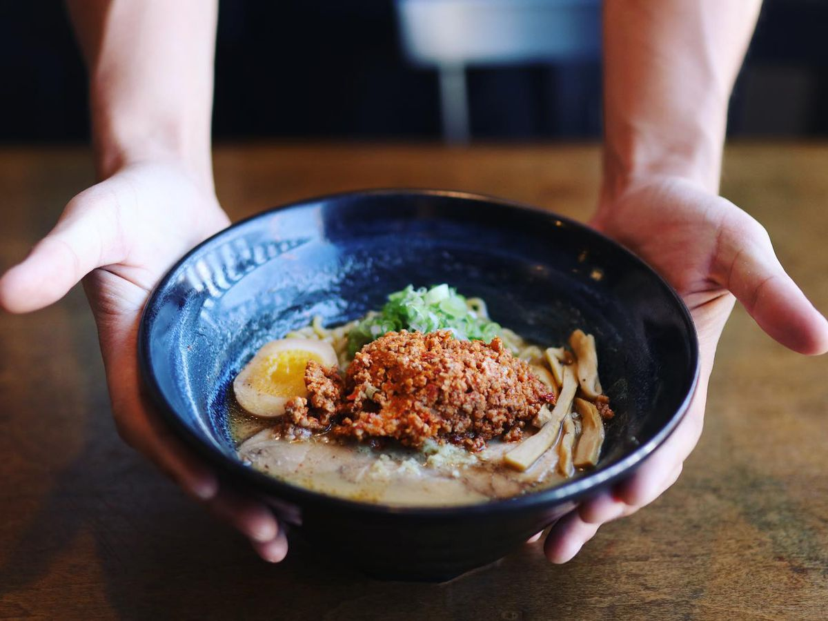 Hands wrapped around bowl of ramen