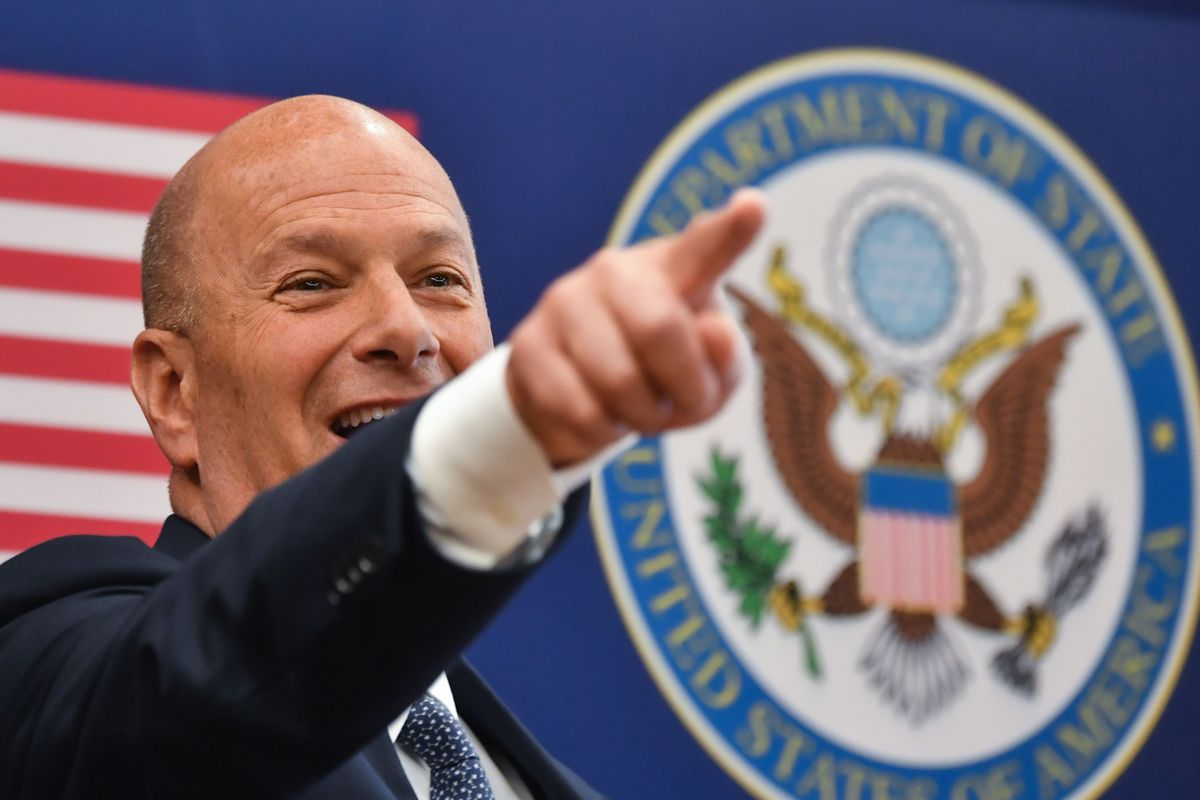 Sondland smiles, pointing, in front of the US flag and State Department seal.