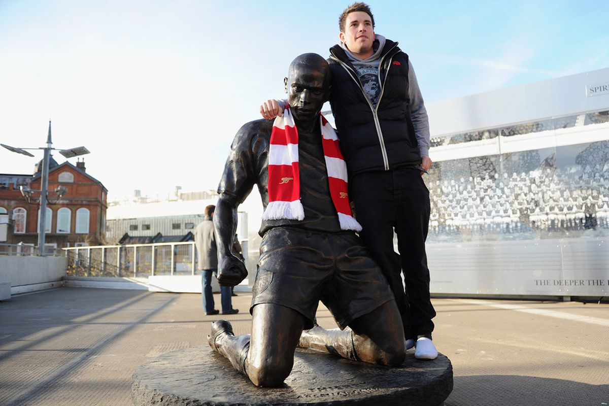 Theirry Henry is now forever immortalized at the Emirates. A fan poses with Henry's statue prior to Arsenal's 1-0 victory over Everton.  (Photo by Michael Regan/Getty Images)