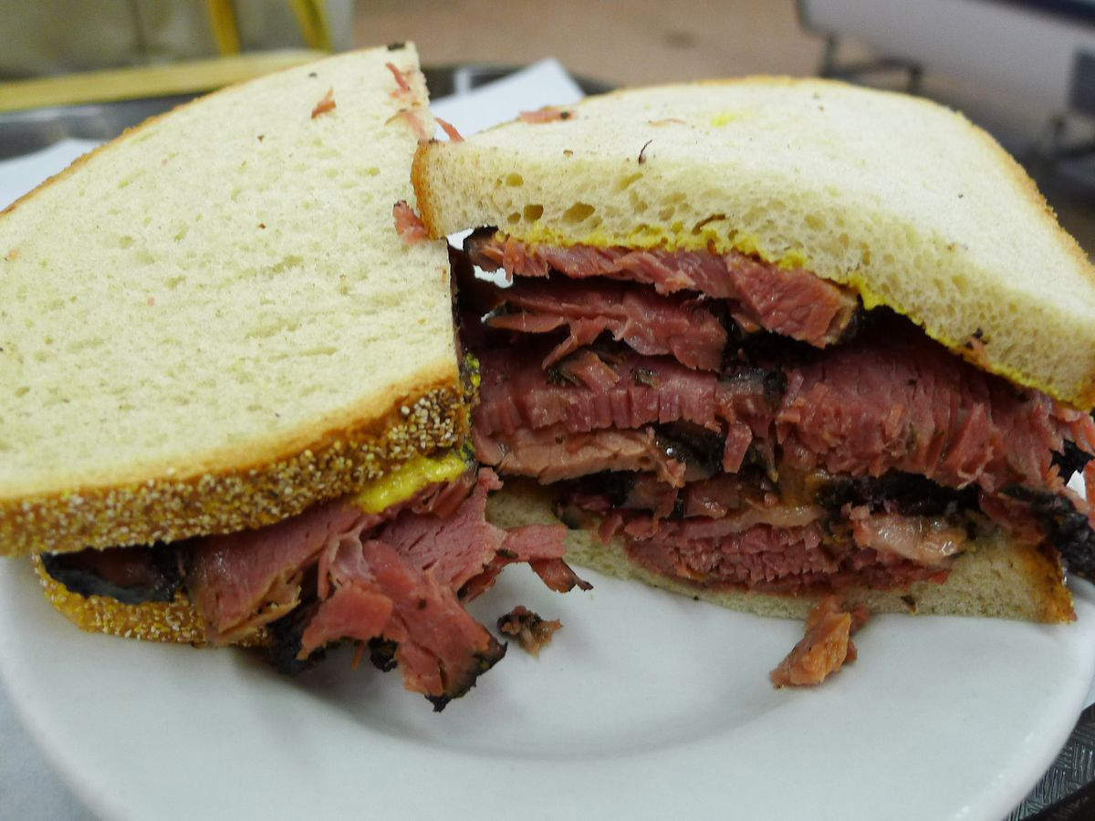 A thick pastrami sandwich on rye is cut in half on a plate.