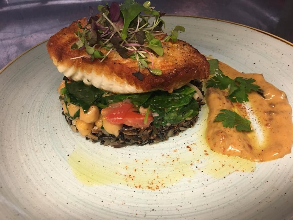 A pan-seared filet of a white fish is garnished with microgreens and sits atop a pile of grains and greens. There's a thick swoosh of a pinkish orange sauce on the side of the white plate.