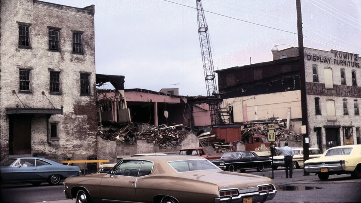 A 1970s photograph of an old brick building on a city block under demolition with a man standing by a street sign and cars passing by.