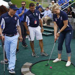 Fox 61's Jimmy Altman and Rich Coppola watch Margaux Farrell putt in the mini golf tournament.