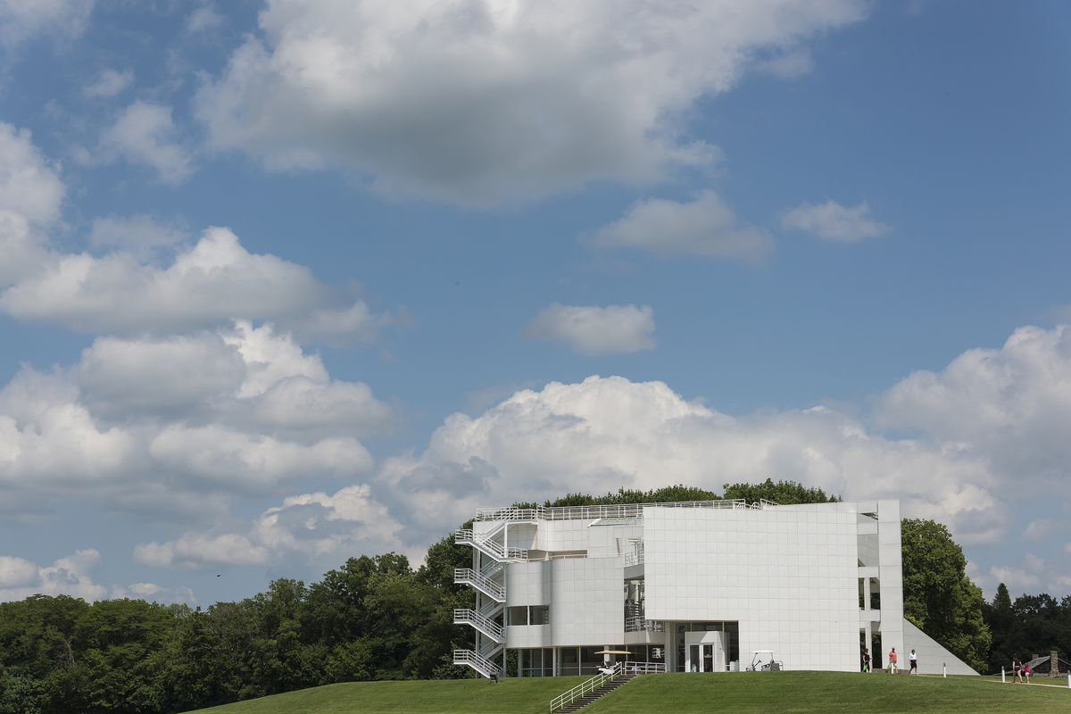 A modernist white building stands against trees and a blue sky with large white clouds.