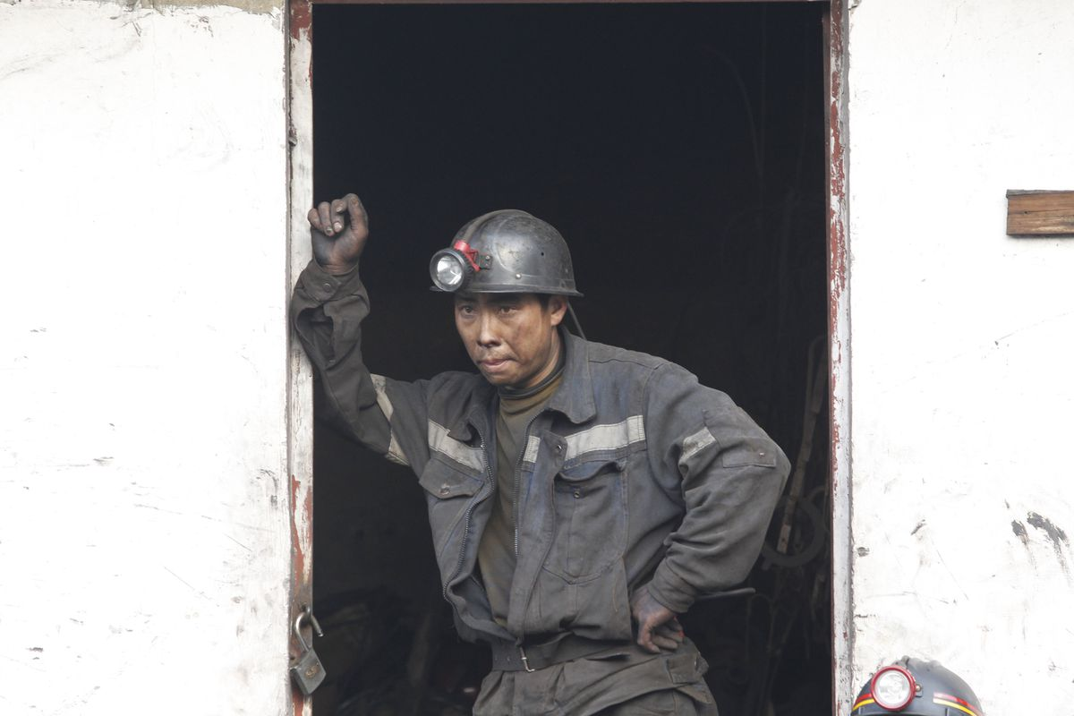 A miner waits for his brothers at a flooded coal mine where 22 miners were trapped underground on April 7, 2014 in Qujing, Yunnan Province of China.