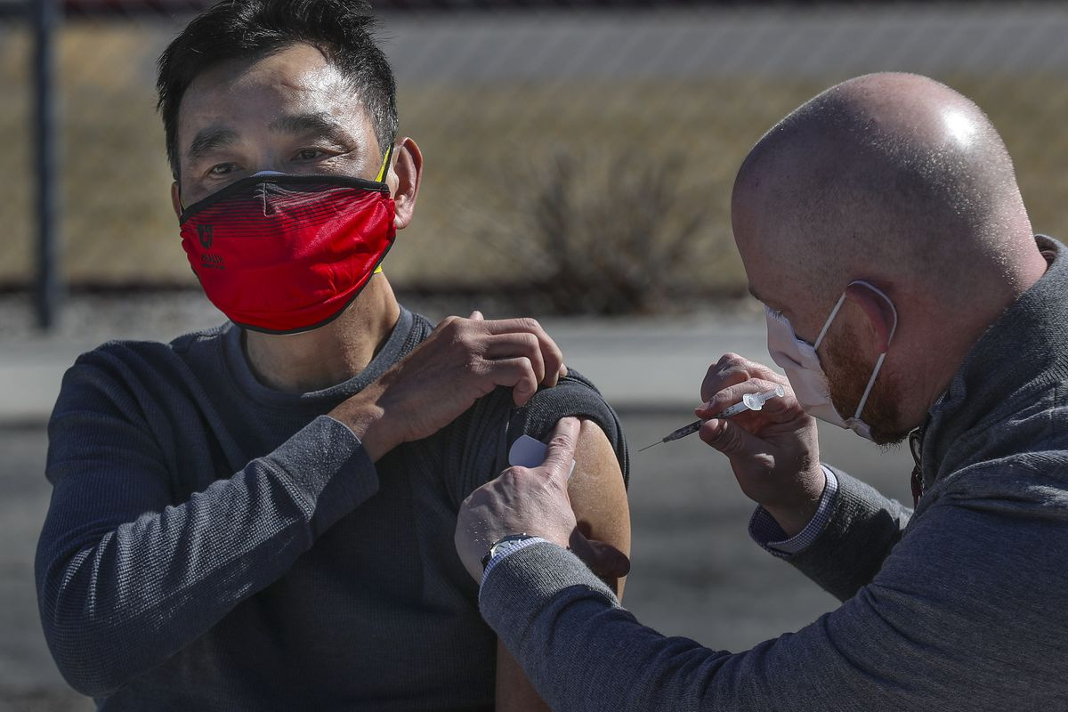 Wyn Choa, a heart transplant recipient, is administered his first dose of the Pfizer COVID-19 vaccine by Nathan Hagen, director of pharmacy for University of Utah Health, at U. Health's Redwood Health Center in Salt Lake City on Monday, March 1, 2021.