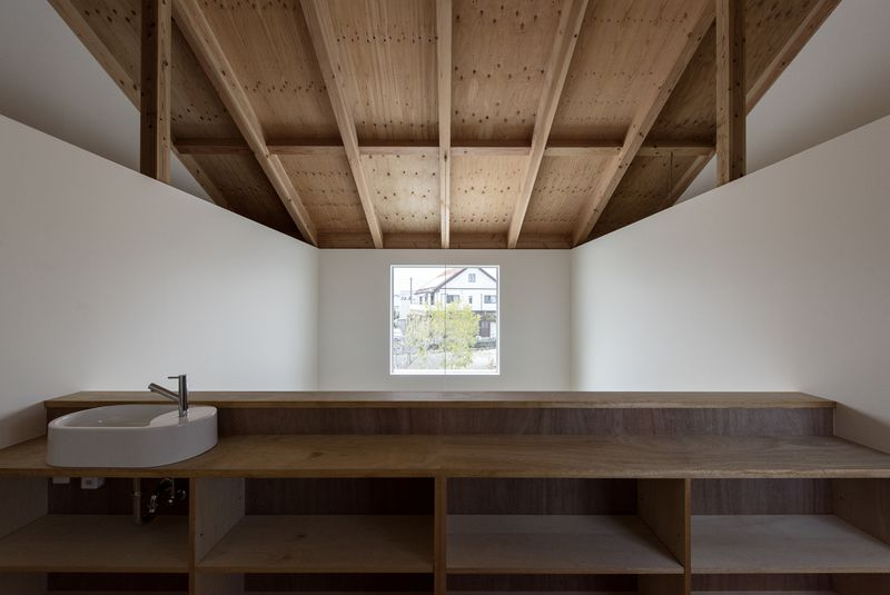 Under timber ceilings, a loft space has a sink and wooden counters overlooking a large picture window.