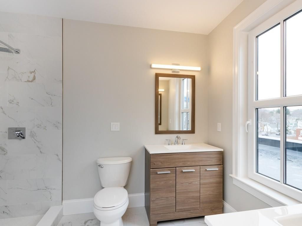 A bathroom with a glass-enclosed shower next to the toilet.