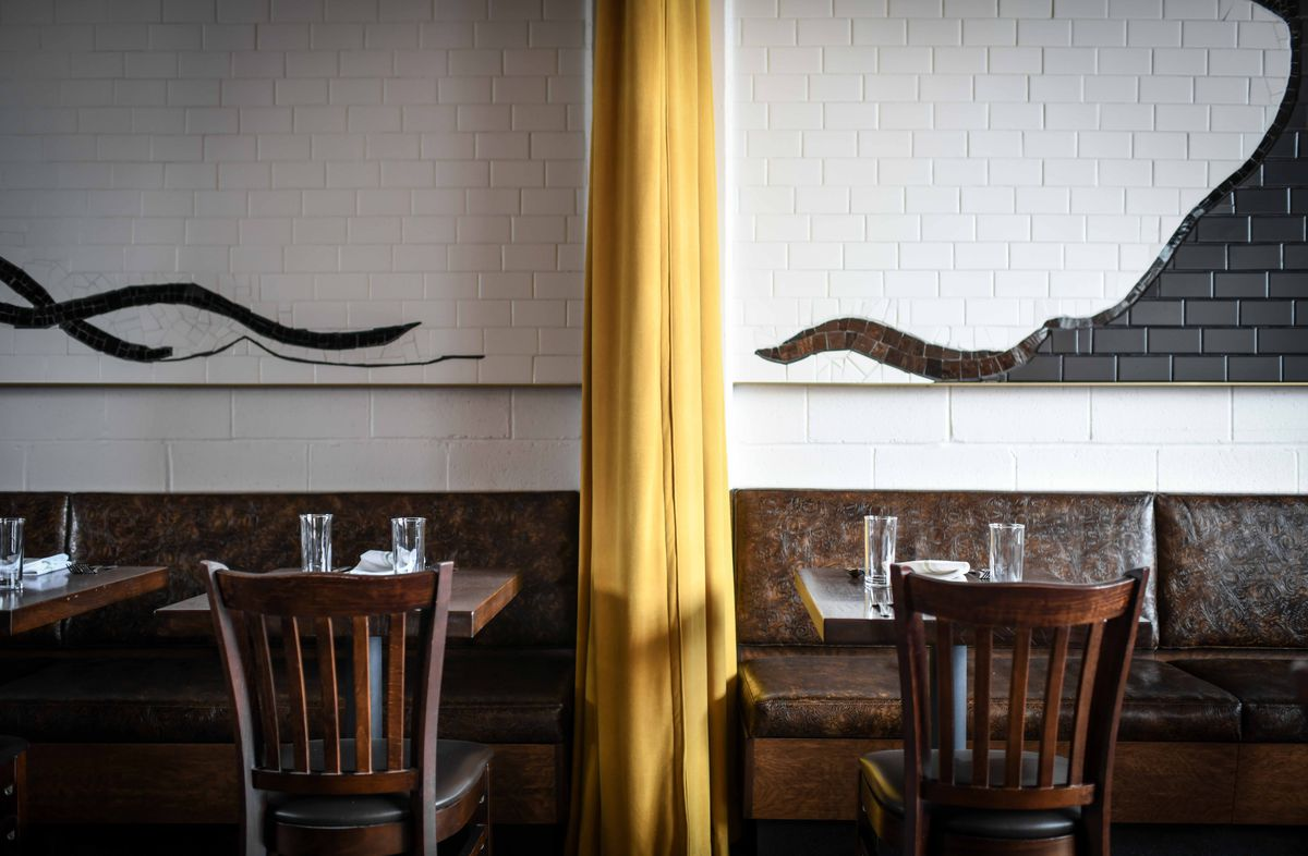 A yellow curtain hangs against a tile mural in Novel's dining room