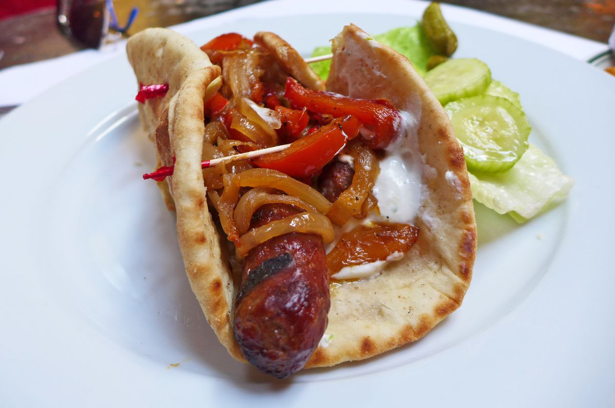 A pita with sausage a peppers inside.