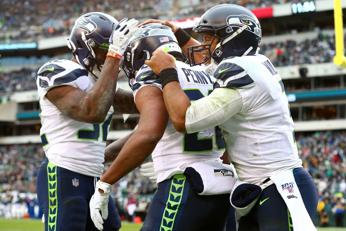 Rashaad Penny of the Seattle Seahawks celebrates with Russell Wilson and Chris Carson after rushing for a fourth quarter touchdown against the Philadelphia Eagles at Lincoln Financial Field on November 24, 2019 in Philadelphia, Pennsylvania.