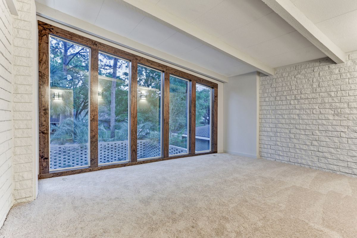 An empty bedroom has white carpet and a wall of windows.