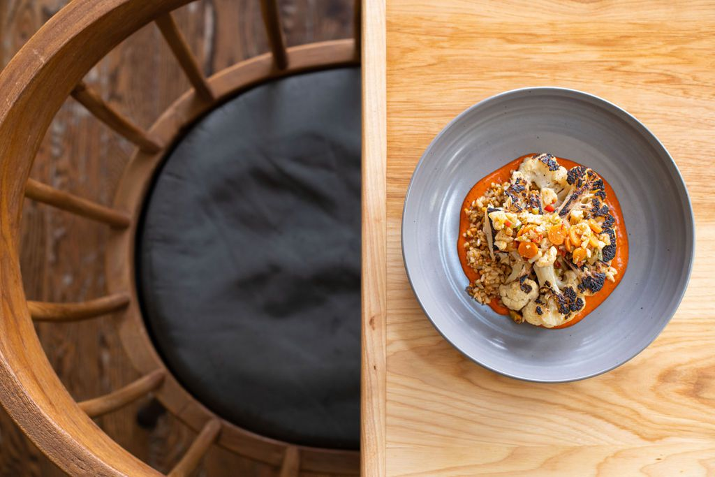 A colorful cauliflower dish sits inside a grey bowl on a light wood table.
