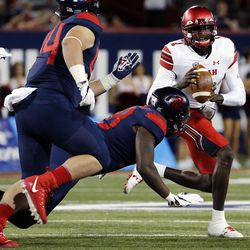 Utah Utes quarterback Tyler Huntley runs the ball with Arizona Wildcats defensive lineman Larry Tharpe Jr. defending in Tucson, Arizona, on Friday, Sept. 22, 2017. Utah beat Arizona 30-24.