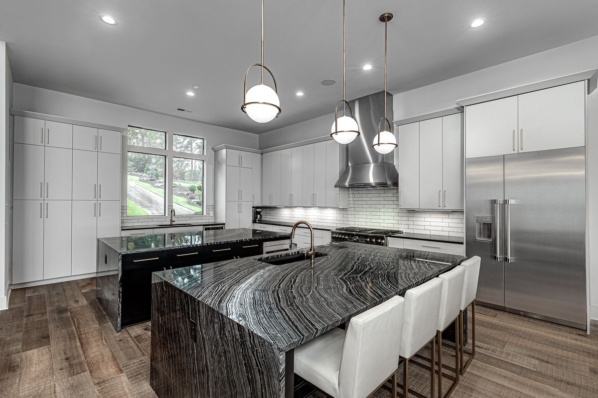 White kitchen with two islands covered in marble countertops and stainless appliances.