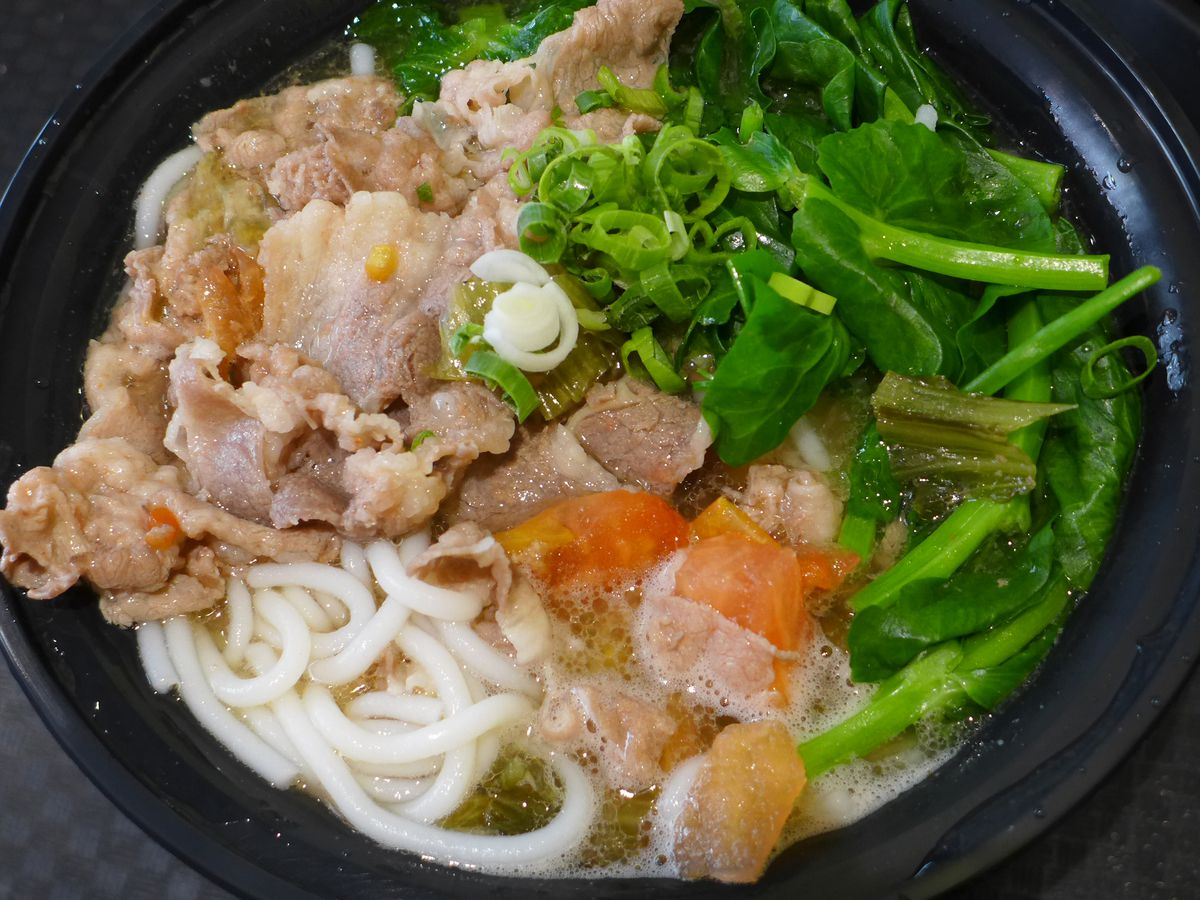 Rice noodles in a bowl with greens and fatty beef.