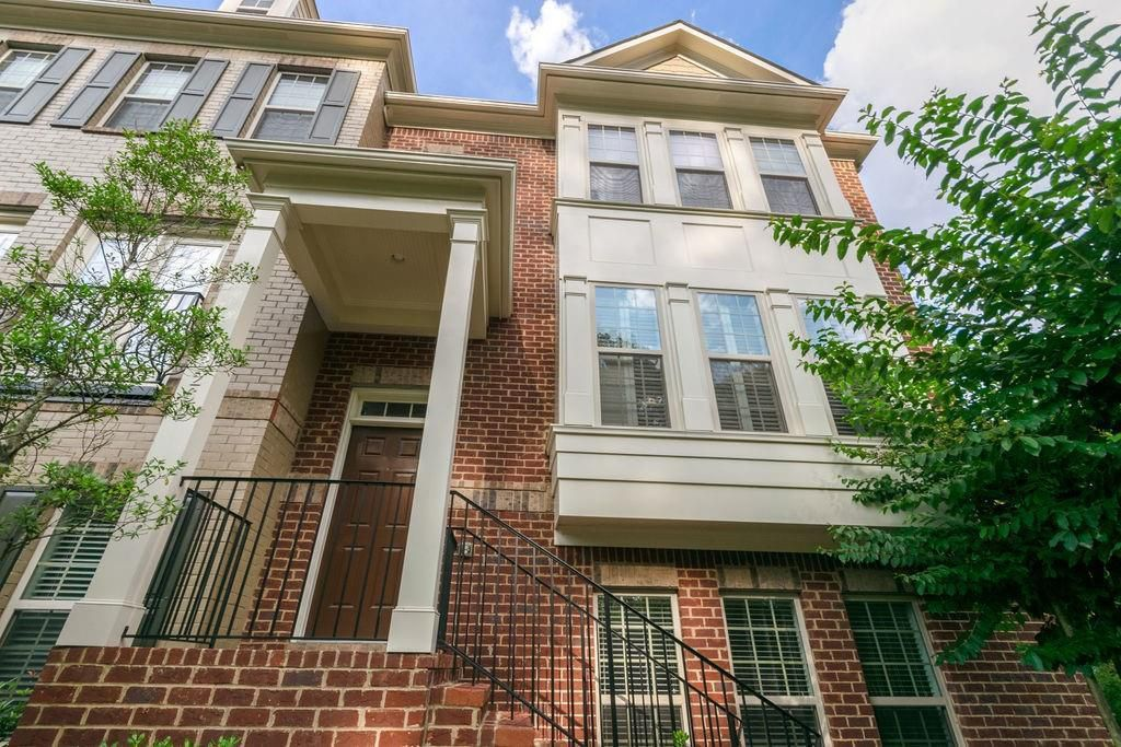 View looking up at three-story brick townhouse with trees on each side.
