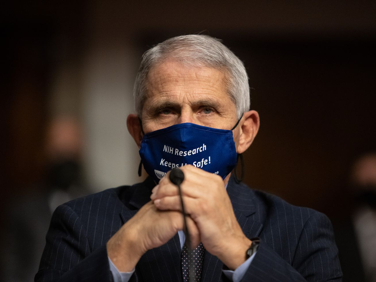 Fauci, in a dark suit and dark blue cloth mask, sits in front of a microphone — without his glasses. His hands are folded in front of his chin.