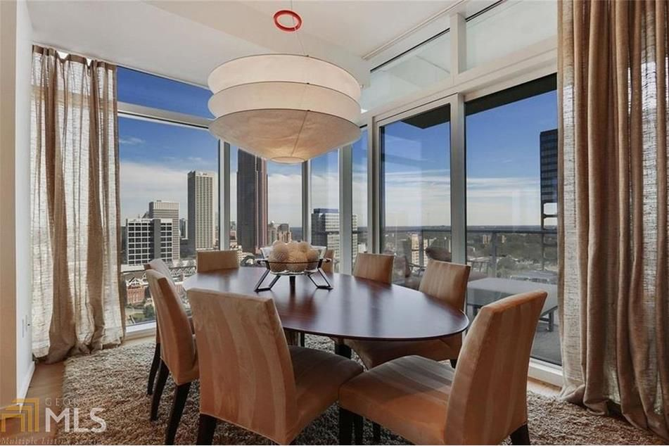 A large dining table with brown chairs and city views.
