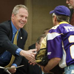 Minnesota Vikings fan Larry Spooner, right, thanks committee chair Geoff Michel after the Senate Jobs and Economic Development Committee moved a proposal forward about the Minnesota Vikings NFL football stadium bill on a voice vote at the state Capitol on Tuesday, April 24, 2012, in St. Paul, Minn. It's due next in the Senate Finance Committee which could be its last stop before a Senate floor vote. The House version of the $1 billion stadium proposal has cleared committees and could get a floor vote as early as Wednesday.