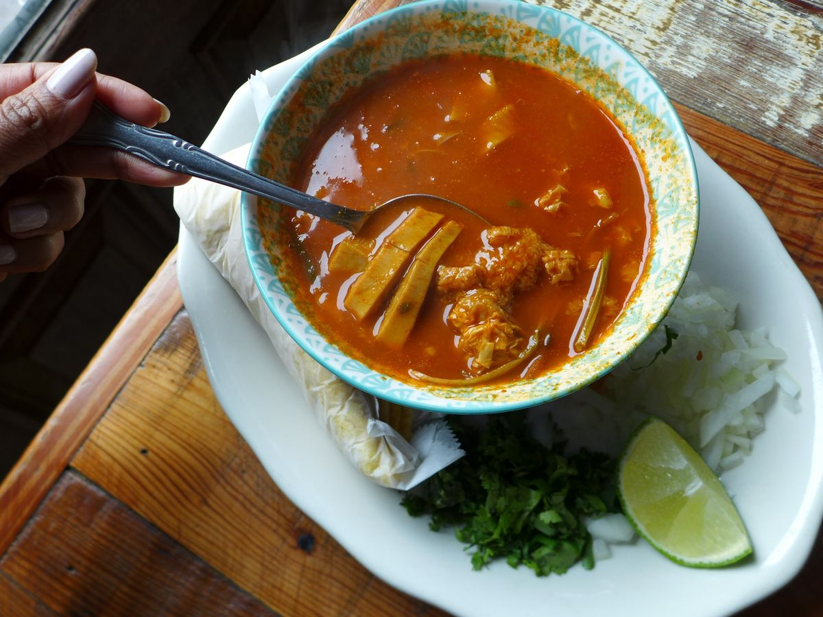 A brick red soup with swatches of tripe