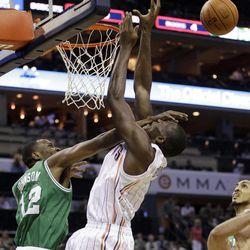 Boston Celtics' JaJuan Johnson, left, fouls Charlotte Bobcats' Bismack Biyombo, right, during the first half of an NBA basketball game in Charlotte, N.C., Sunday, April 15, 2012.