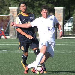 Conor Bradley dribbles the ball with Carlos Cuevas on his back