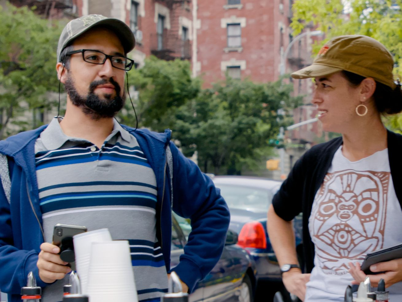 A man and a woman stand talking to one another on a film set.